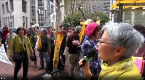 Chizu Hamada of the No Nukes Action Committee speaks at the second rally in front of PG&E Headquarters after the march from the protest at the Japanese Consulate in San Francisco on 3-11-15.  Screenshot from the video at IWJ-SF Ustream channel.