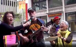 Cynthia Papermaster holds the mic and sings along with Vic Sadot and Chizu Hamada at the Japanese Consulate protest by No Nukes Action Committee for the 4th Anniversary of the Catastrophic and Ongoing Disaster at the Fukushima Nuclear Complex on March 11, 2011. Vic has a new verse for Fukushima.