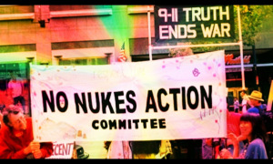 "Screenshot from the video features two signs during a demonstration. One for ""No Nukes Action Committee"" and one for Northern California 9/11 Truth Alliance that says ""9/11 Truth Ends War""."